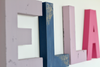 Boho girls nursery name sign for ELLA in purple, blue, and pink.