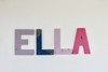 Boho custom name sign spelling out ELLA in different shades of purple and pink pastel colors.