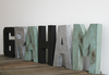 Industrial nursery name letters spelling out Graham in black, silver, and distressed patina green colors.