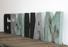 Industrial nursery name letters spelling out boys name Graham in different colors such as black, silver, and a distressed patina green.