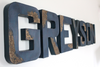 Navy blue distressed letters spelling out Greyson.