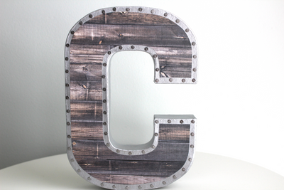 Industrial nursery wall letter C featuring a nail trim design.