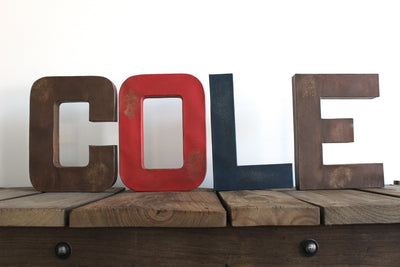 "Woodland theme nursery name COLE in ""wooden"" letters"