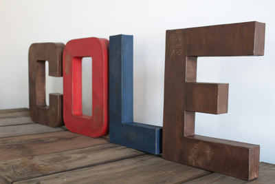 Bear theme nursery custom wall letters spelling out Cole in distressed brown, red, and navy colors.