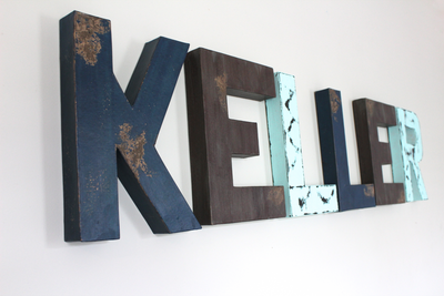 Little boy room custom wall letters spelling out the name Keller in blues and browns.