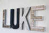 Boy room decor customized wall letters spelling out the name LUKE that was handprinted in different colors such as navy, silver, white, and brown.