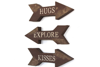 Three wooden style letters pointing in different directions with the word explore, hugs, and kisses.