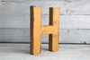 "Mustard yellow ""wooden"" letter H in a  distressed style"