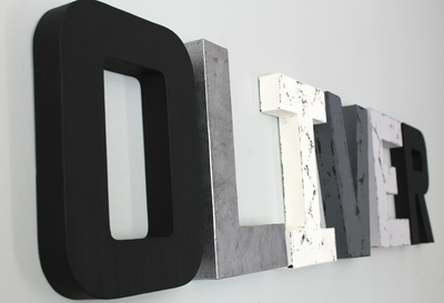 Black and white nursery letters in black, white, and different shades of gray spelling out Oliver.