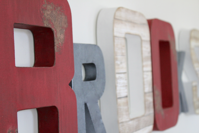 Distressed red wall letters and gray faux metal letters spelling out the name Brooks for a woodland and firetruck themed nursery.