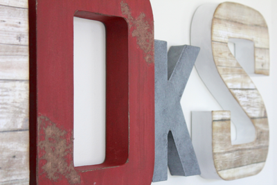 Red and white distressed letters with a gray faux metal letter accent for boys woodland nursery wall decor.