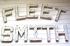 "White ""wooden"" letters spelling out FLEET SMITH for wedding tabletop decor"
