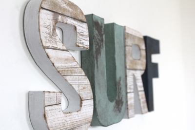 Surf wall decor letters in a faux reclaimed white wood and blue letters.