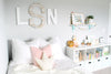 "Cute little girls bedroom with a large white ""wooden"" monogram with the letters LSN."
