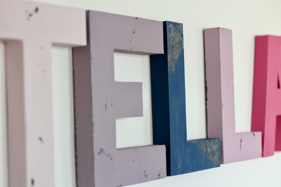 Name letters in pinks, purples, and navy for girls room decor.