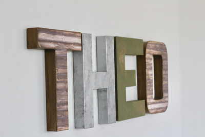 Theo nursery letters in brown, silver, and green.