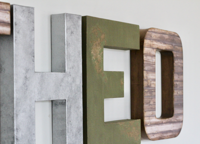 Rustic letters in silver, green, and brown.