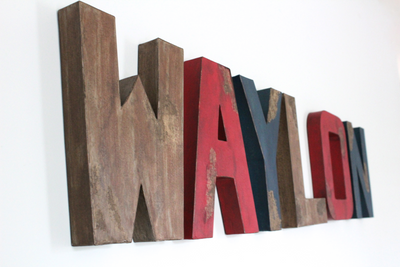 Custom wall letters for camping themed nursery wall decor spelling out the name letters Waylon in distressed brown, red, and navy colors.
