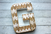 White chevron wooden letter G in a tribal style chevron pattern