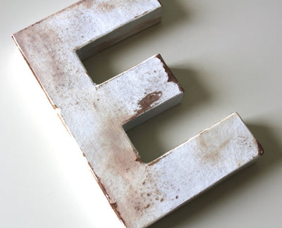"Distressed white ""wooden"" letter E in a rusty look"