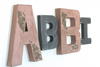 Pink Industrial girl name letters in different sizes and colors.