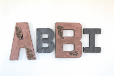Pink and silver nursery name letters spelling out the girl's name Abbi.