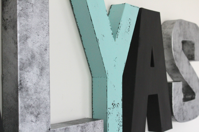 Modern wall letters in black, silver, and patina blue.