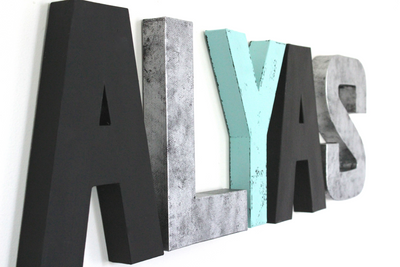 Monochrome nursery wall letters in black, silver, and teal spelling out the name Alyas.