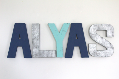 Modern wall letters spelling out the name Alyas in blue wall letters and industrial silver colors.