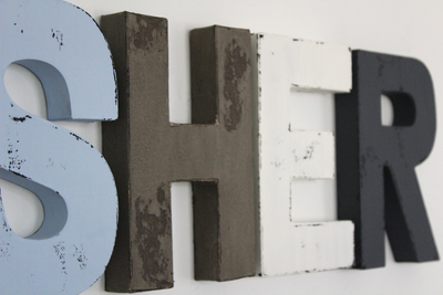 """Wooden"" nursery wall letters in blue, grey, and white."