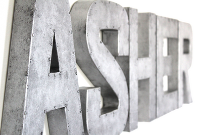 Galvanized letters spelling out Asher in silver wall letters.