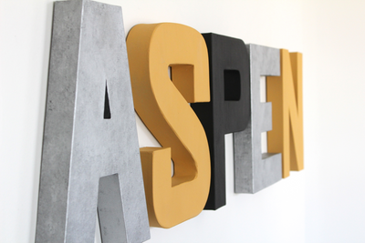 Modern nursery name sign spelling out the name ASPEN in black, silver, and yellow.
