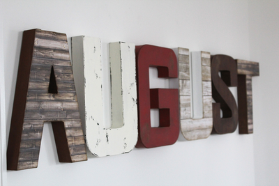 "Distressed ""wooden"" letter boy name AUGUST in a brown ""wood"", white, and red color"