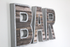 Industrial farmhouse bar wall sign with nails going around the letters.