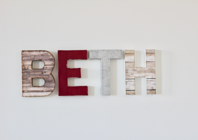 Girls name sign spelling out BETH in brown, purple, silver, and white.