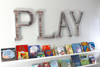 Kids playroom wall decor spelling out the word PLAY in large letters.
