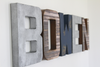 Rustic industrial nursery letters spelling out Bowen in brown, silver, and navy colors.