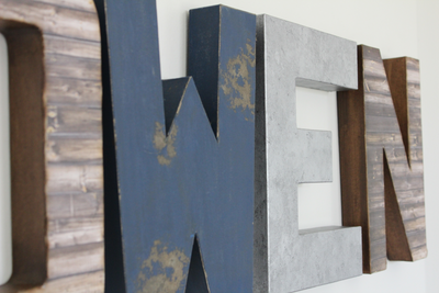 Nursery letters in distressed brown, navy, and silver colors.