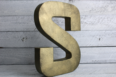 metal brass letter S on a wooden pallet for room decor