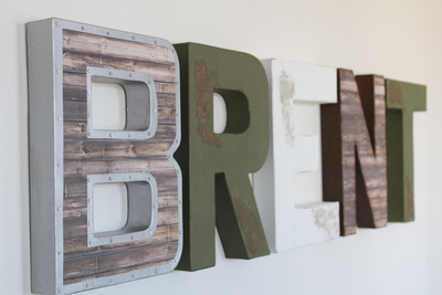 Rustic farmhouse wall letters spelling out the name BRENT in brown, green, and white letters.