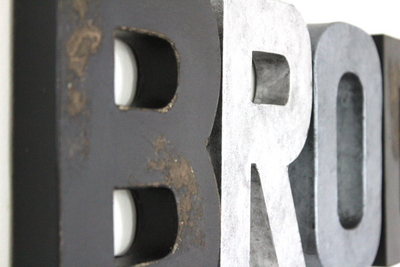 Black distressed letter B and silver and grey letters.