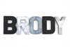 Boy name wall letters spelling out BRODY in distressed black letters and silver and grey monochromatic letters.