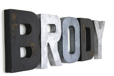 Monochromatic black, silver, and grey letters spelling out BRODY.