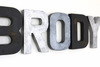 Modern farmhouse nursery letters spelling Brody in black distressed letters and industrial silver and grey letters.