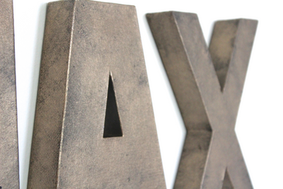 Bronze wall letters A and X.