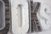 Brown and white rustic letters trimmed with silver nails.