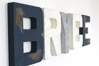 Boy name sign in navy, silver, and white spelling out the name Bryce.