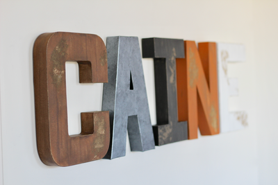 Caine basketball nursery letters in brown, grey, black, and orange.