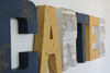 Carter custom wall letters for lion nursery wall decor in three different rustic colors like navy, yellow, and beige.