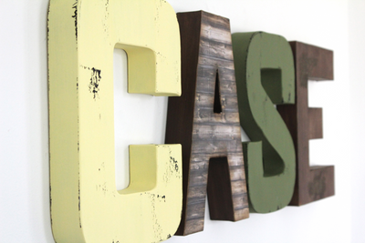 Custom wall letters for farm animal nursery decor spelling out CASE in yellow, brown, and green for baby boy nursery wall decor.